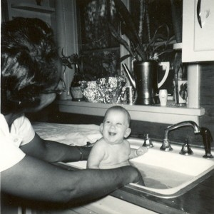Steve Reese as a baby having a bath in the kitchen sink