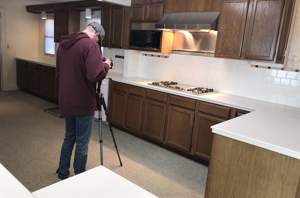 professional photographer is setting up shot of cooktop in a kitchen