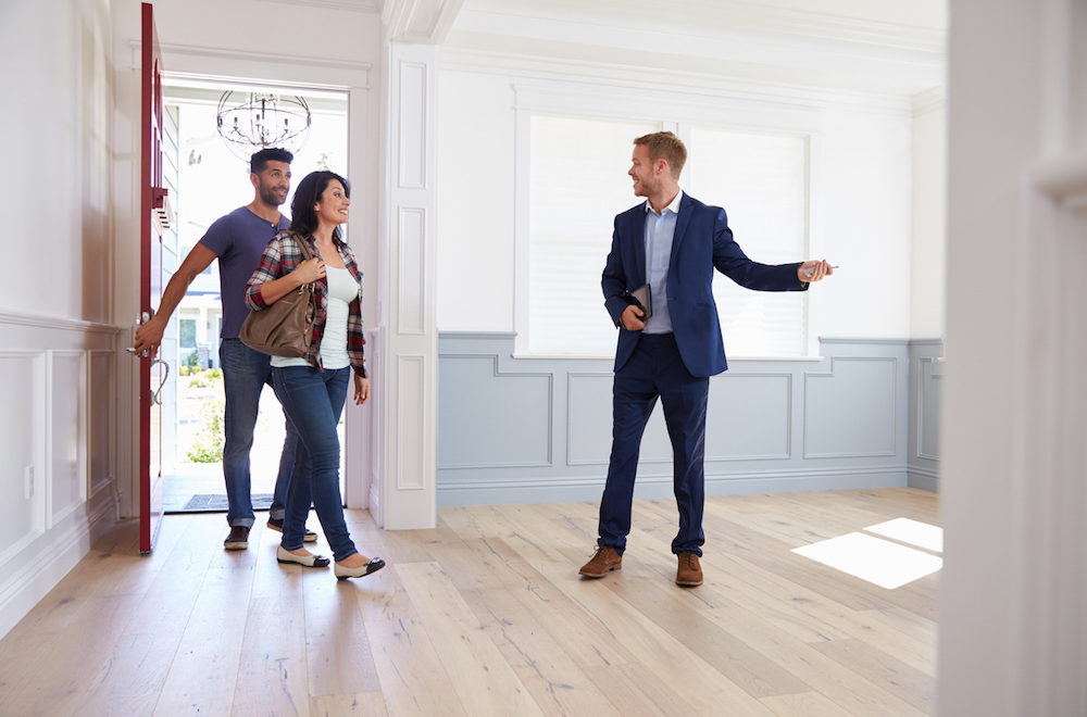 agent taking homebuyers into house for final walk-through inspection