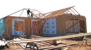 home under construction with framers on the roof