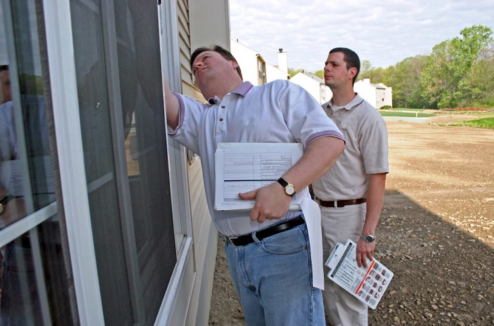Two home inspectors examining around a window on the exterior of a house