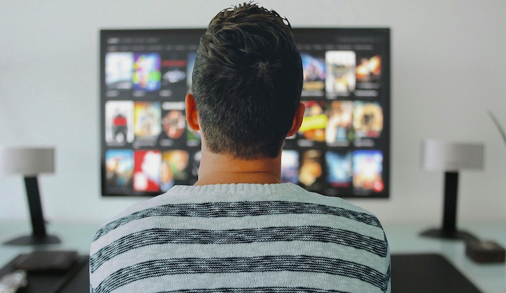 Back of man's head watching streaming menu of programs on TV mounted on wall