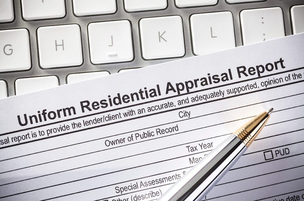 Uniform Residential Appraisal Report and pen on a computer keyboard