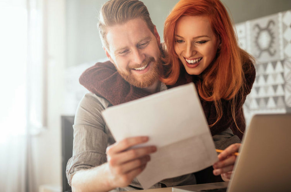 Couple looking at paperwork - file for your homestead exemption to save money on your property taxes