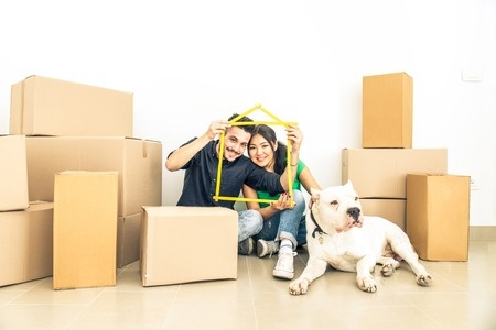 Happy couple with dog moving to a new home