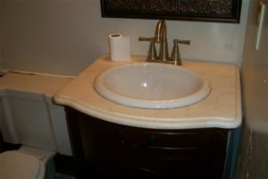 actual MLS photo of a bathroom sink and toilet with a partial roll of toilet paper on the vanity.