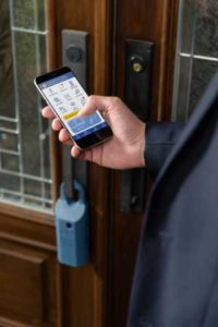 Realtor using mobile app to access Supra eKey lockbox on front door of house