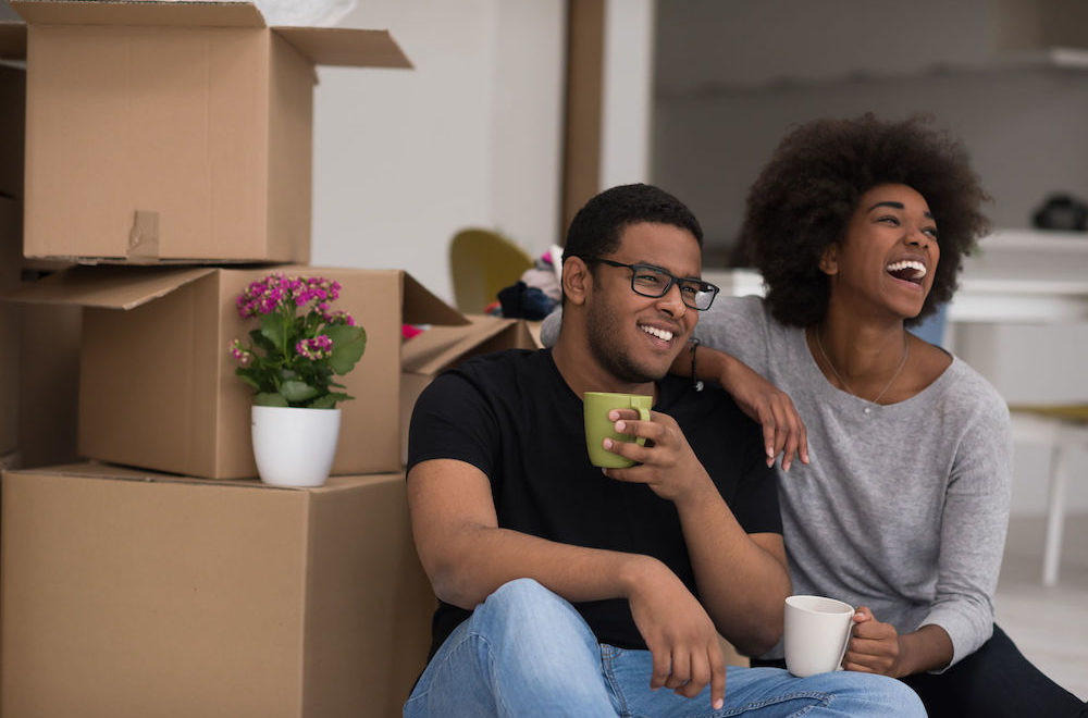 smiling young couple sitting in front of moving boxes drinking coffee