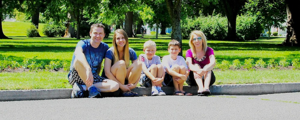 Family sitting on the curb in front of a city park