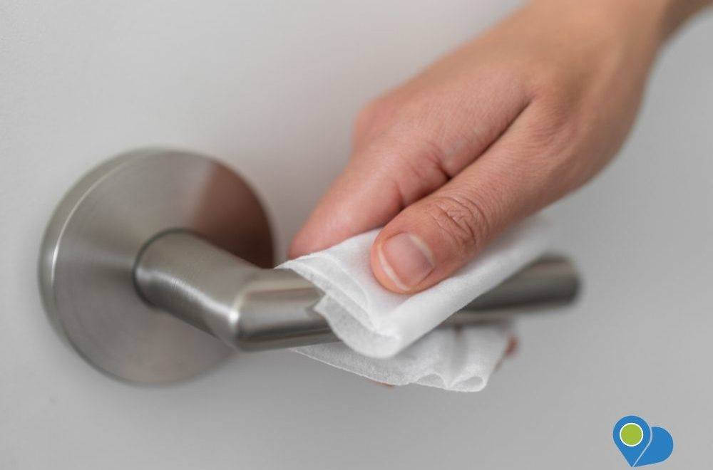 opening door knob using sanitizing towel as a preventive measure for coronavirus